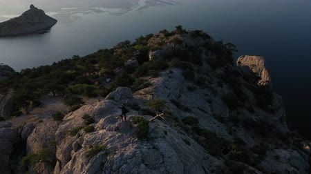 альпинист : Successful woman mountaineer on mountaintop in Crimea with arms outstretched. Aerial silhouette of young woman standing on the top of a mountain against the sea at sunrise. Lady on the summit Стоковые видеозаписи