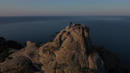 krím : Aerial silhouette of young Successful woman standing on the top of a mountain against the sea at sunrise. Woman mountaineer on mountaintop in Crimea with arms outstretched.
