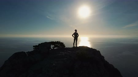 альпинист : Aerial silhouette of young Successful confident woman mountaineer on mountaintop in Crimea with arms outstretched. Brave Woman standing on the top of a mountain against the sea at sunset.