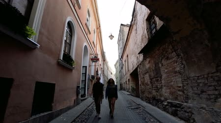 vilnius old town : Walk along ancient streets of a European city. Two young women walking on the narrow streets of Vilnius old town. Two young women walk in the city of Vilnius old town. Stock Footage