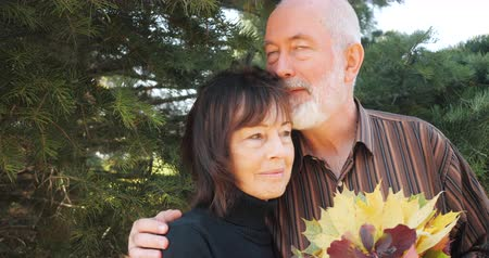 stary : Happy elderly couple man and woman with a bouquet of leaves hugging in autumn under a pine tree - slow motion.