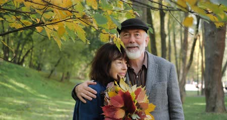 darling : Happy elderly couple in hugs enjoys autumn in a cozy park among the trees - slow motion.