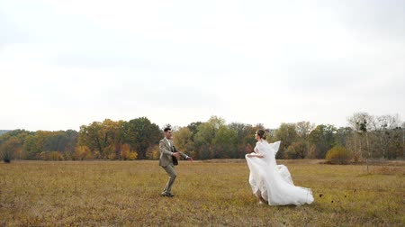 núpcias : Young attractive Bride and Groom run to each other in Slow motion along an autumn field and meet against colorful forest . Tracking shot of Groom spinning beautiful Bride around in rural landscape.