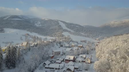 baita : Mountain village in snow from a height. Flight over a village in Carpathian mountains in winter at sunrise. Aerial view of snow-covered houses, ski resort in mountains. Rural landscape in winter.