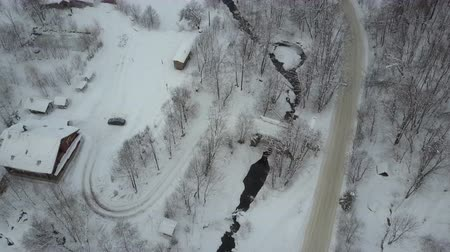 faház : Flight over a village in Carpathian mountains and a ski resort next to it. Aerial Winter road along a river and houses under snow in mountain village. Rural landscape in winter. Carpathian ski resort.
