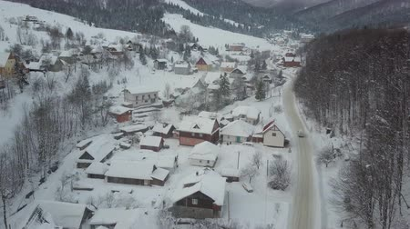 baita : Aerial Winter road along a river and houses under snow in mountain village. Car moves in winter through a village in Carpathian mountains to a ski resort. Rural landscape in winter.