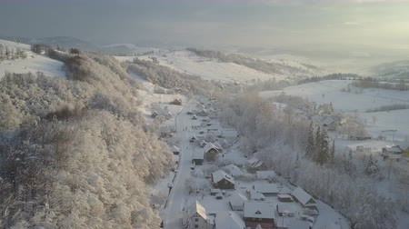 chata : Aerial panorama of a mountain village in winter at sunrise. Houses under snow in mountain village. Rural landscape in winter. Flight over a village in Carpathian mountains and a ski resort next to it.