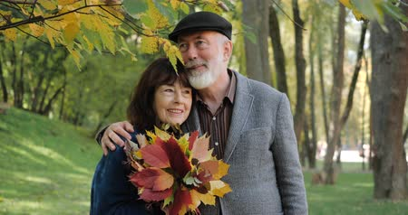darling : An elderly couple laughs with happiness, cuddle and enjoy a sunny autumn day in a cozy park among the trees - slow motion. Active modern life after retirement. Smiling with happiness. Stock Footage