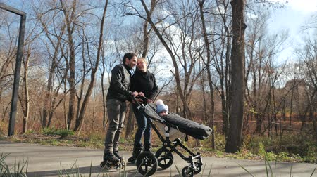 rolki : Family performance in the autumn park, roller blades and stroller. Dad catches up with mom and gives her a stroller. Parents on Roller skates with a child in Slow motion.