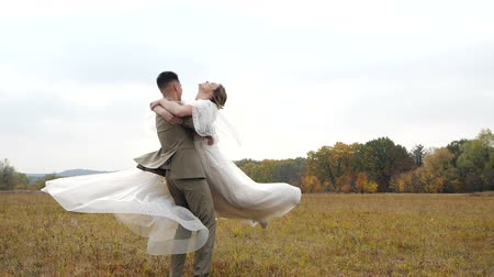 núpcias : Young Groom spins attractive Bride around in the centre of an autumn field. Happy loving newlyweds in rural landscape on the background of Colored fall trees. Groom spinning Bride in rural landscape.