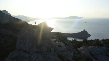 альпинист : Young active woman on top of a mountain in Crimea with arms outstretched. Aerial silhouette of young woman standing on the top of a mountain over the sea at sunrise. Lady mountaineer on the summit