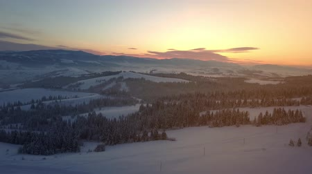 surroundings : Flight over Carpathian mountains in winter at sunrise. Rural landscape in winter from a height. Aerial view of a snow-covered mountains.