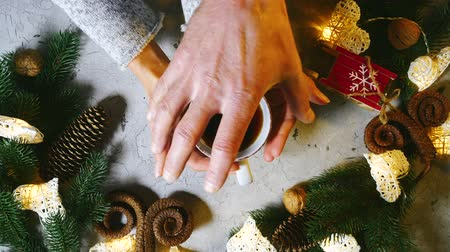застежка : Christmas is a family holiday. Beautiful female hands put a cup of black tea or coffe on the table, male hands clasp female ones. On the table are Christmas decorations, spruce branches of a garland