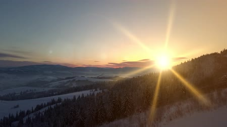 baita : Flight over Carpathian mountains in winter at sunrise. Aerial view of a snow-covered mountain. Rural landscape in winter from a height.