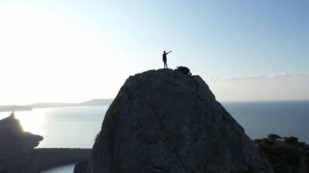 climber rock : Aerial silhouette of young woman waving her hand standing on the top of a mountain over the sea at sunrise. Young active woman on top of a mountain in Crimea. Lady mountaineer on the summit Filmati Stock