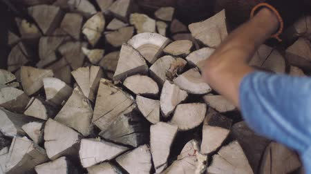 упакованный : Stacked wood is dried and prepared for cold winter months. Man puts chopped wood pieces neatly onto one each other in a pile. Dry woods are packed in a heap for a fireplace.