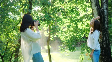 fotoğrafçı : Pretty girl professional photographer wearing white shirt is making photos of a happy smiling girl in a park next to a birch tree on a soft background of green foliage and spraying water. Stok Video