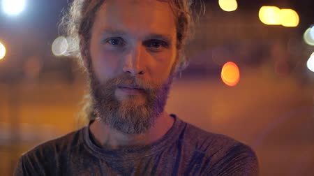 intruder : Close up, Portrait of a handsome Caucasian bearded young man with long hair looking calm straight to the camera on the background of moving evening lights of a city.