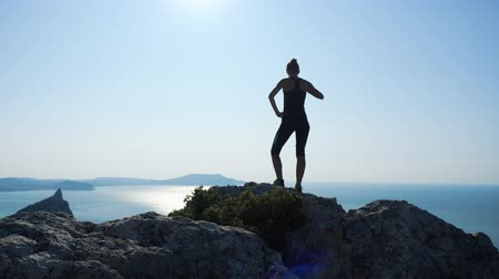 krím : Silhouette of a happy hiker woman standing on the summit with a cup of tea and enjoying fantastic view from a height on a sea against beautiful blue sky. Stock mozgókép