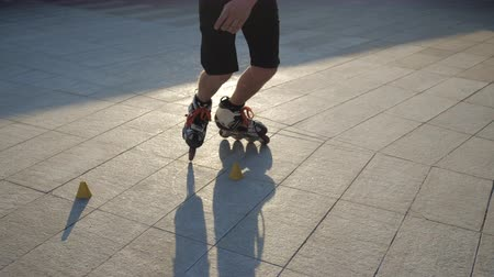 roller blading : Close-up legs of a young man professionally skating between cones on a nice evening sunset in a city park. Freestyle slalom Roller skating between cones. Stock Footage