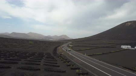 vinná réva : Drone shot of cars and bicycles moving by a road among vineyards on black volcanic soil in Lanzarote. Aerial scenic view of Wine growing in La Geria on Lanzarote, Canary Islands, Spain.
