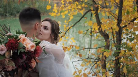 juntar : Close-up portrait of Groom and bride hugging near a lake in autumn forest among Colored fall trees. Young attractive Happy loving newlyweds in a park in Slow motion.