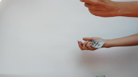 ganancioso : Womans hands catch two 100 US Dollar banknotes falling in slow motion against white background.