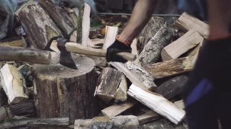 hatchet : A man woodcutter chops tree trunks with an ax for firewood. Man chops wood outdoors in slow motion. Mans hands working with ax. Stock Footage