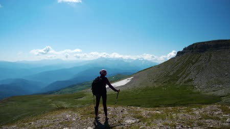 épico : Lady hikes in beautiful Caucasian mountains. Young woman with backpack and trekking poles on the way to the mountain top makes a pause to observe fantastic view from a height.