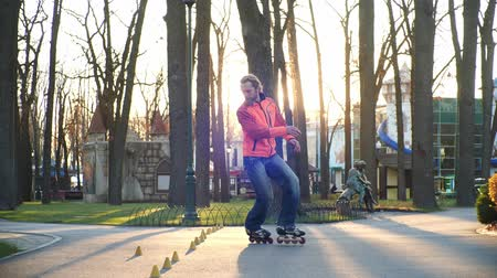 roller blading : Training of a professional roller who skillfully skates in the central park of the city and performs complex turns between training cones. Active and healthy lifestyle. Side view in slow motion.