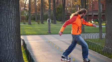 roller blading : Sports man on roller skates deftly and successfully goes around cones for training, riding back and forth and showing the most complicated riding technique. Autumn training in a city park slow motion. Stock Footage