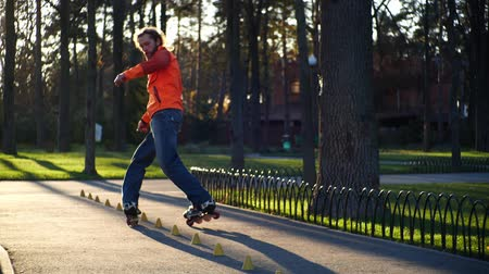 roller blading : A professional male roller rides great backwards, crossing his legs and riding between the cones, then stands on two rear wheels. A man performs a technical roller skate ride in slow motion.