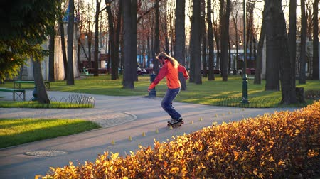 krzew : Sporty and useful rollerblading. A man professionally trains on roller skates, rides between training cones and performs complex turns in the city park in the last days of autumn. Slow motion.