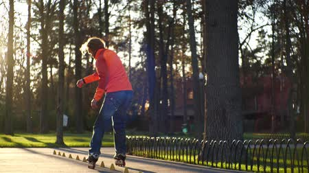roller blading : Bearded man on roller skates performs a complicated technique of roller skating, performs various turns and tricks. Training with special cones for rollers. Sport and healthy lifestyle slow motion. Stock Footage