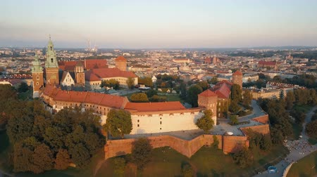 wawel : Aerial view of Royal Wawel Cathedral and castle in Krakow, Poland, with Vistula river, park, yard and tourists at sunset. Old city in the background Stock Footage