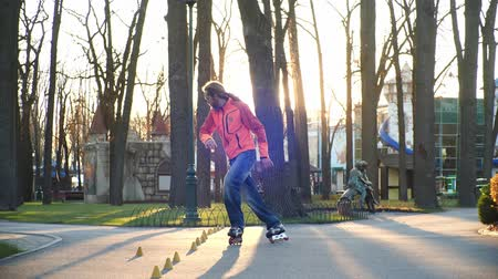 rolki : Rollers are a mans favorite hobby. A professional roller masterfully performs a difficult ride on the pavement of a city park in the sunny weather of an autumn day. Bottom-up shooting in slow motion. Wideo
