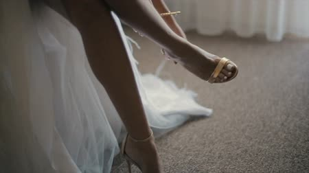 elkötelezettség : Bride wears her wedding shoes. Wedding morning. Close-up elegant womans sandals on a girls thin leg.