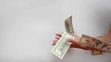 ganancioso : Womans hands try to catch falling US Dollar banknotes falling in slow motion against white background.