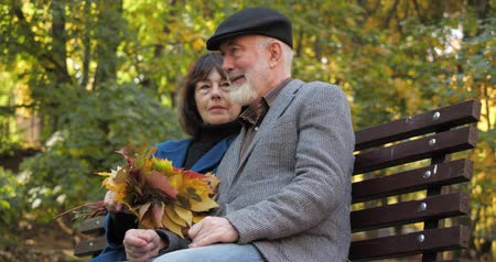 stary : Happy elderly family spends leisure sitting on a bench in the fresh air of an autumn city park. The wife strokes her husband with a bouquet of autumn leaves. Gatherings on the street in slow motion.