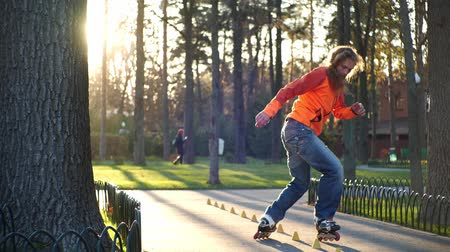 roller blading : The man sits on the roller blades, straightens the training cone and stands on his feet making a deft turn. The concept of an active and healthy life in slow motion. A ray of sun shines into the camera.