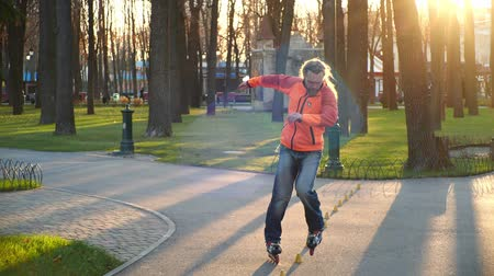 roller blading : A professional roller rides great backwards on roller skates between training cones, crossing legs. Active and sporting leisure in the central park of the city. Bottom-up shooting in slow motion. Stock Footage