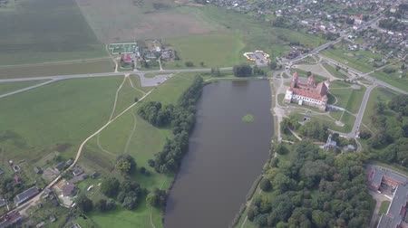 altezza : Aerial shot with a quadcopter of Mir Castle in Belarus slow motion. The lake is located near Mir Castle. Ancient and beautiful landmarks of Belarus, recommended for visiting. Filmati Stock
