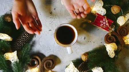 ennek : Against the background of fir branches, cones, Christmas and New Year decorations, female hands put a cup of tea or coffe on the table, after which the male hand takes this cup for.