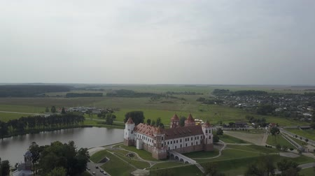 small height : Circular aerial photography from quadcopter of the Mir Castle in Belarus, which is located in the town of Mir, surrounded by trees and is located near a small lake. Top view in slow motion.