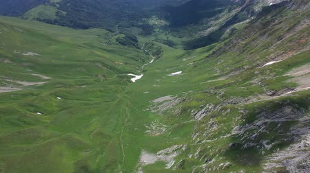 назад : Flying backward over a mountain valley in Mountains of Adygea on summer day. Green trees and bushes among rocks and snow fields. Wild nature seen from above.