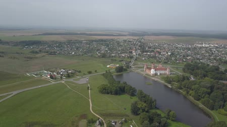 citadela : Shot from above the village of Mir and Mir Castle in Belarus in slow motion. Ancient pride and sight in autumn from a birds eye view. Panorama of a small village and an old building, top view. Dostupné videozáznamy