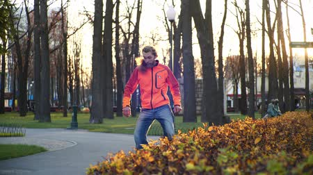 roller blading : A professional male roller dances on roller blades in slow motion in a comfortable city park in the last days of autumn. Idea of outdoor activities and a healthy lifestyle.