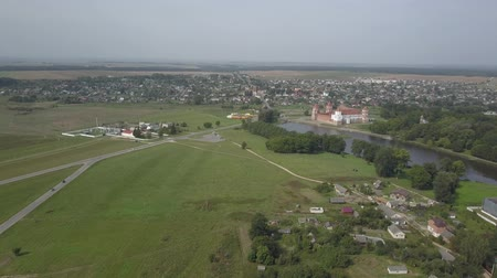small height : Shot from above the village of Mir and Mir Castle in Belarus in slow motion. Ancient pride and sight in autumn from a birds eye view. Panorama of a small village and an old building, top view. Stock Footage
