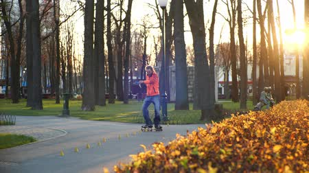 roller blading : Professional bearded roller conducts daytime training in an autumn city cozy park, makes complex turns and tricks. Active and healthy lifestyle. Shooting from under the bushes in slow motion. Stock Footage