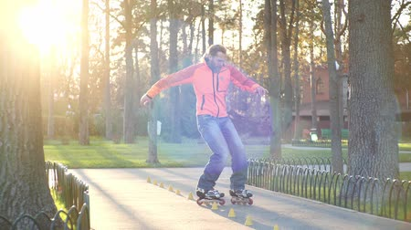 roller blading : Professional skater trains his bypass skills between special cones and makes complex technical turns. Roller skate training in sunny weather in autumn. Active and athletic lifestyle in slow motion. Stock Footage